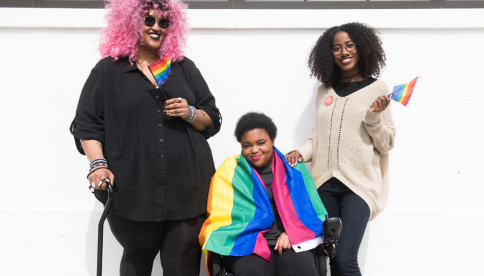 Three Black and disabled folx smiling with rainbow pride flags. On the left, a non-binary person holds a cane in one hand and waves a mini flag in the other. In the middle, a woman sits in her power wheelchair with a large flag draped around her shoulder. On the right, a woman rests one hand on her friend's shoulder and waves a mini flag around with the other.