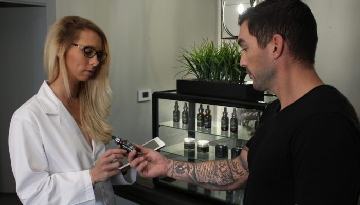 Photo: A white woman in a lab coat helps a white man with many tattoos, wearing a black t-shirt, select a CBD oil product in a dispensary.