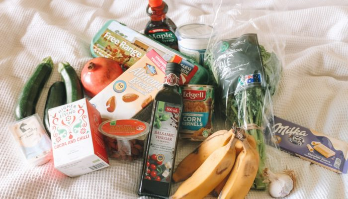 Do deliveries pose a risk for immunocompromised people? How can you offer safe mutual aid to your neighbors? Photo: A collection of groceries arrayed on a sheet including almond milk, bananas, zucchini, a pomegranite and various other staples.,