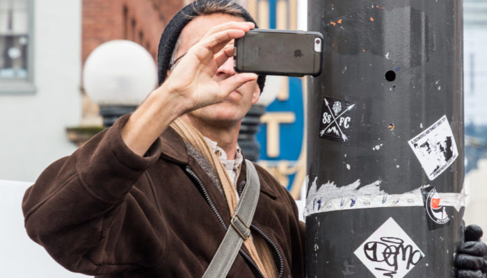 A citizen journalist hangs on a light pole to get a better view of a protest as he films on a smartphone.