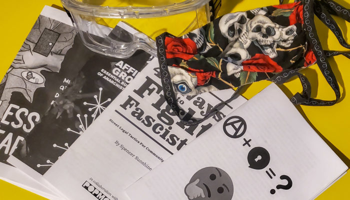 A set of protective goggles and a cloth mask with roses and skulls sit on a yellow surface near 4 zines, the main selections from this edition of the virtual zine library, which are fanned out in an arc.