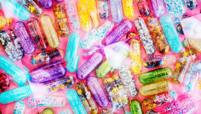 Softgel capsules full of glitter and sparkly confetti.