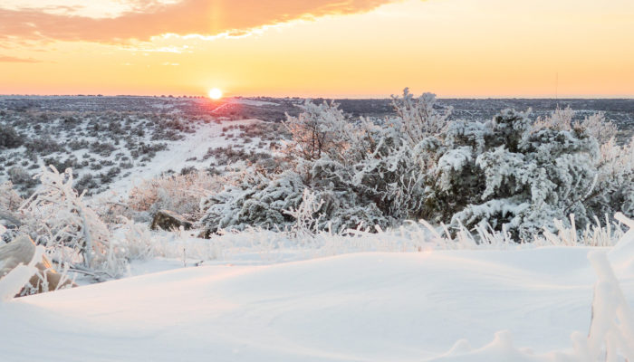 The sun sets over a snow and ice covered field in rural Texas, February 15, 2021.